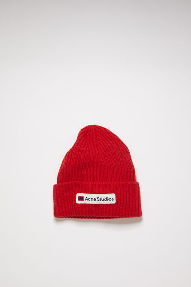 Acne Studios red beanie is knitted in a thick rib-stitch from soft wool and features an embroidered logo patch on the turn-up.