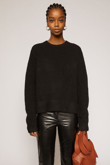 Acne Studios black sweater is crafted from wool-blend and finished with ribbed trims and a side-slit hem.