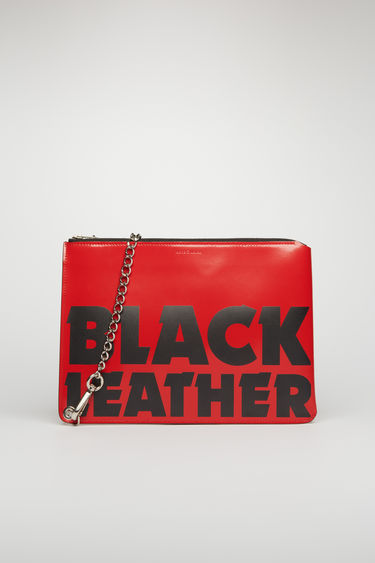 "Acne Studios red/black pouch is crafted from high-shine leather and printed with the words ""Black Leather"" across the front. Secured with a zip fastening and chain, the compact accessory holds space for documents and small essentials."