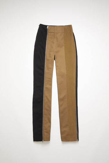 Acne Studios beige/black panel trousers are crafted from repurposed black rigid denim and brown brushed cotton twill, featuring zip details on both legs. Shaped to sit high on the waist with straight legs.
