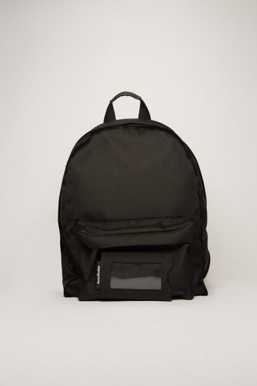 Acne Studios black backpack is crafted to a structured silhouette with a front zip pocket and features an adjustable crossbody strap, woven zip pullers and a transparent card pocket.