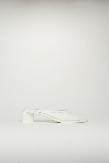 Acne Studios white/white open-toe mules are crafted from grained leather with a wide strap across the front, then set on a triangular block heel.