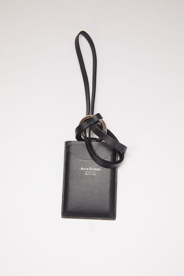 Acne Studios black lanyard card holder is made of smooth leather with two card slots and a silver stamped logo on the front.