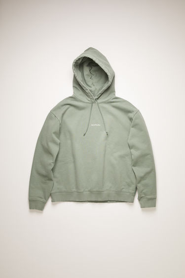 Acne Studios dusty green hooded sweatshirt is made from organic cotton that's lightly faded along the seams. It's cut to a relaxed silhouette with dropped shoulders and ribbed edges and features a raised logo print on front.