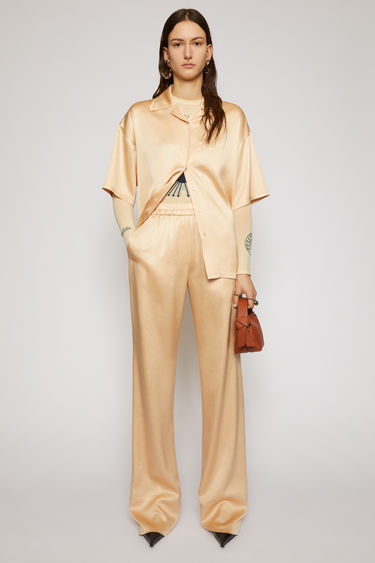 Acne Studios pale orange satin trousers are tailored in a straight-leg shape that drapes loosely over the leg and finished with an elasticated waistband with drawstrings on the side.