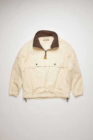Acne Studios champagne beige jacket is crafted from a technical matte shell with front pocket, drawstring hem and a half-zip collar and features a repeating 'Acne Studios' logo across the front.
