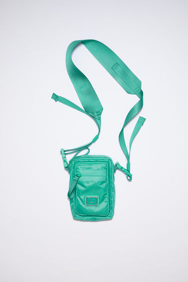 Acne Studios jade green pocket bag is made from technical ripstop with a detachable crossbody strap and an array of zipper and mesh pockets, accented with a polished metal logo plaque with a face motif in black.