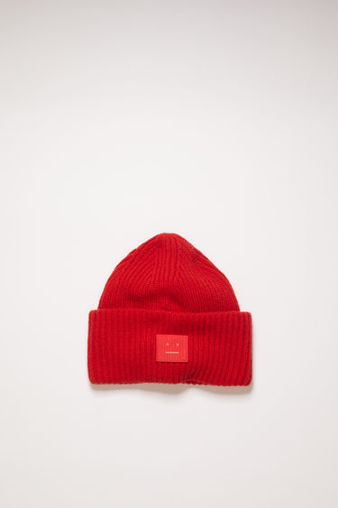 Acne Studios red beanie is knitted in a thick rib-stitch from soft wool and features a tonal face-embroidered patch on the turn-up.