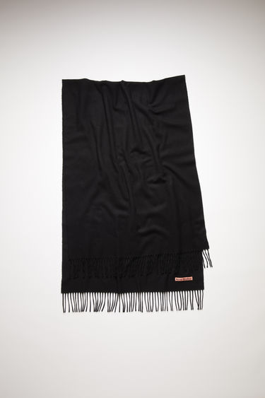 Acne Studios black oversized fringed scarf is made of cashmere, featuring a label in one corner.