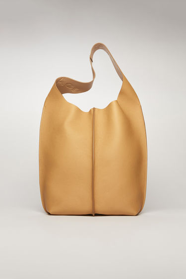 Acne Studios almond beige tote bag is crafted from supple grain leather and has a silver-tone metal clasp which opens to reveal a spacious logo-embossed leather lining with a detachable zip pouch.