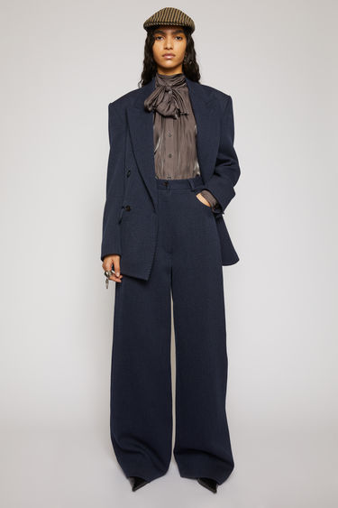 Acne Studios navy/black jumbo twill trousers take cues from men's workwear garments. They're tailored in a wide-leg shape that drapes loosely over the leg and designed with a traditional five-pocket design.