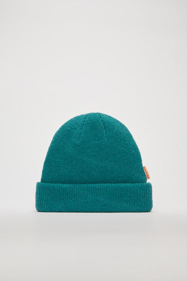 Acne Studios turquoise blue beanie is rib-knitted from a soft wool-blend and accented with a logo tab on the side seam.