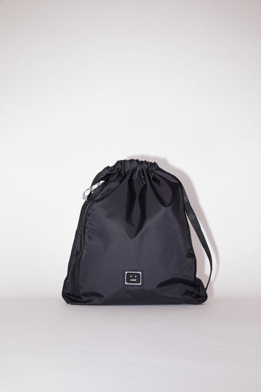 Acne Studios black drawstring bag is made from technical ripstop with face logo straps, accented with a polished metal logo plaque with a face motif in black. It has an interior zipper pocket and exterior pocket with a contrasting face logo zipper pull.