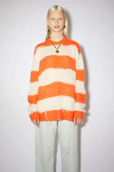 Acne Studios off white/coral sweater is designed in an oversized shape with extended sleeves and patterned with jagged block stripes. It's shaped with a thick ribbed collar and features distressing around the hem and cuffs.