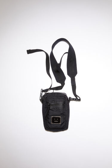Acne Studios black pocket bag is made from technical ripstop with a detachable crossbody strap and an array of zipper and mesh pockets, accented with a polished metal logo plaque with a face motif in black.