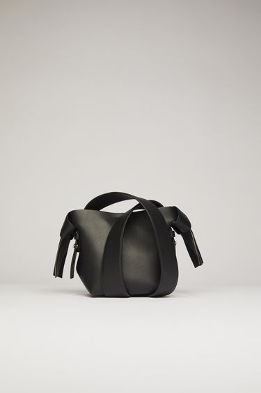 Acne Studios Musubi Micro black bag features knotted details inspired by the traditional Japanese obi sash. It's crafted from soft grain leather and comes equipped with a detachable shoulder strap and a top handle.