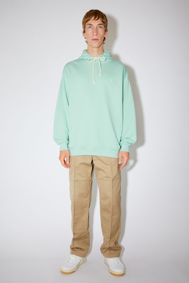 Acne Studios spearmint green oversized hooded sweatshirt is made of organic cotton with a face logo patch and ribbed details.