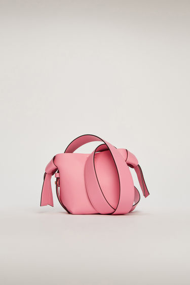 Acne Studios Musubi Micro pink/black bag features knotted details inspired by the traditional Japanese obi sash. It's crafted from soft grain leather and comes equipped with a detachable shoulder strap and a top handle.