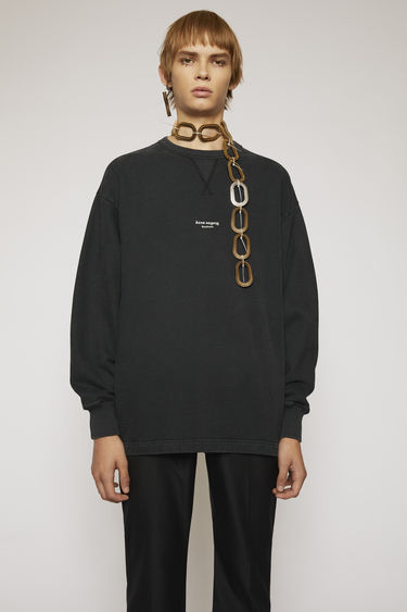 Acne Studios black sweatshirt made from heavyweight brushed jersey that has been garment dyed for a soft, washed-out finish. It has a ribbed v-insert below the crew neck and a reversed logo printed across the chest.