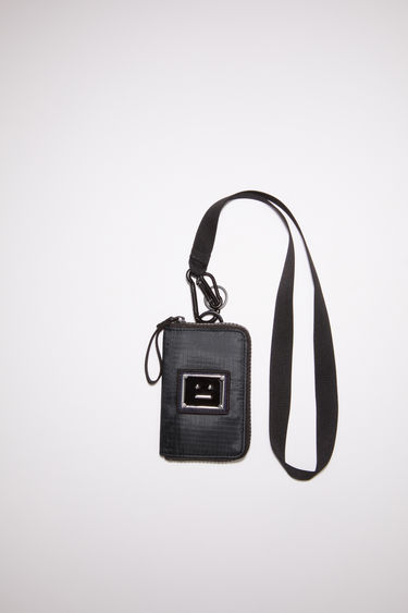 Acne Studios black pouch bag is made from technical ripstop with a detachable lanyard. It has a zipper closure with a pull and is accented with a polished metal logo plaque with a face motif in black.