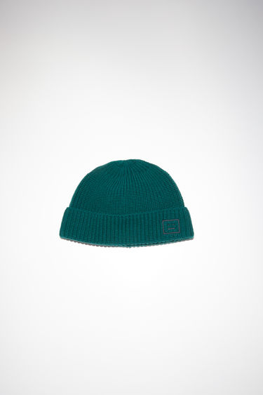 Acne Studios deep green fisherman beanie hat is made from rib knit wool with a face logo patch.