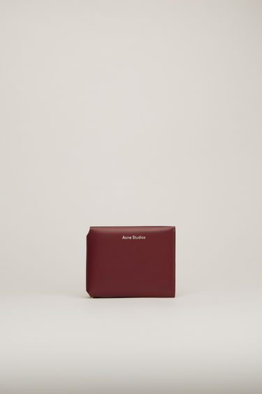 Acne Studios burgundy trifold card wallet is crafted from soft grained leather with a coin pocket, note sleeve and four card slots and features a silver stamped logo on front.