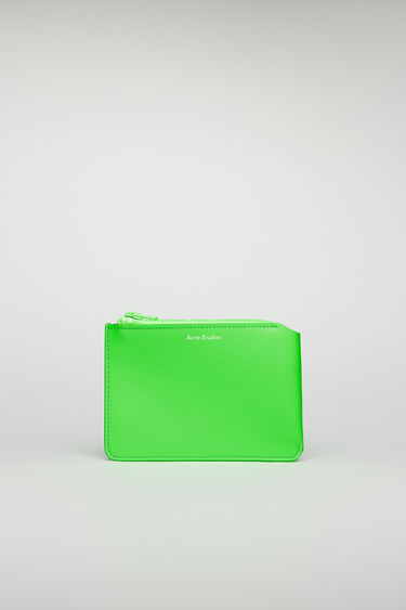 Acne Studios fluo green zip wallet is crafted from cow leather with a matte finish and then accented with a branded zip closure.