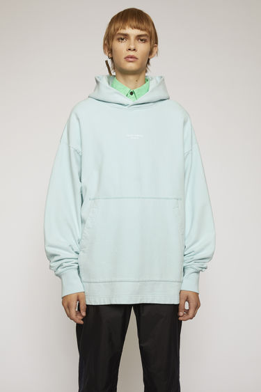 Acne Studios powder blue hooded sweatshirt is made from brushed cotton jersey that has been garment dyed for a soft, washed-out finish and features a reversed logo printed across the chest.