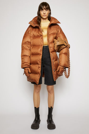 Acne Studios mink brown puffer coat is crafted from recycled down and feather-filled shell and is shaped to an oversized silhouette with softly rounded shoulders. The funnel collar has a packaway hood and is finished with an adjustable belt for a personalised fit.