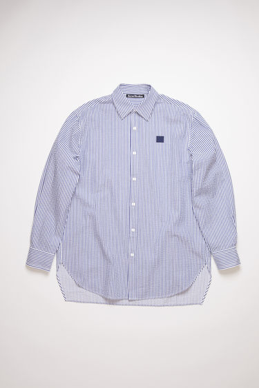 Acne Studios white/blue striped button down shirt is made of cotton with a face logo patch at the chest.