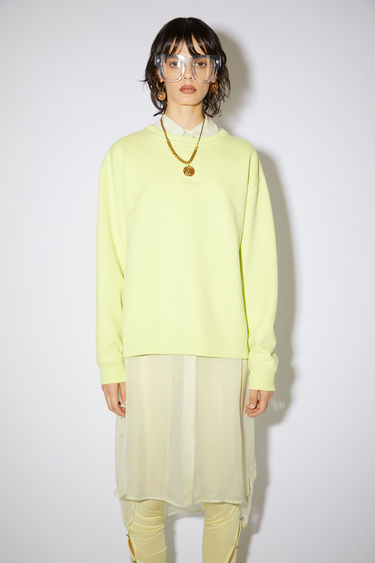Acne Studios lemon yellow crew neck sweatshirt is made of cotton with an Acne Studios logo at the centre chest.
