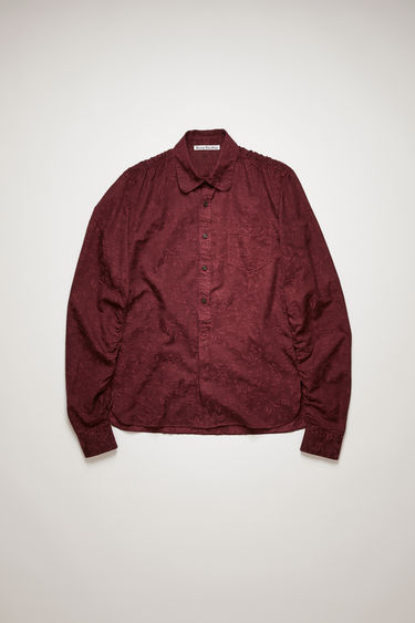 Acne Studios burgundy shirt is made from a soft blend of cotton and cupro that's woven with a floral pattern. It has a fluid drape and silk-like sheen and crafted with a rounded point collar and shirred yoke.