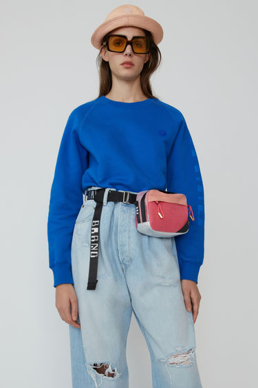 Acne Studios Blå Konst ocean blue raglan sleeve sweatshirt with branding down one sleeve.