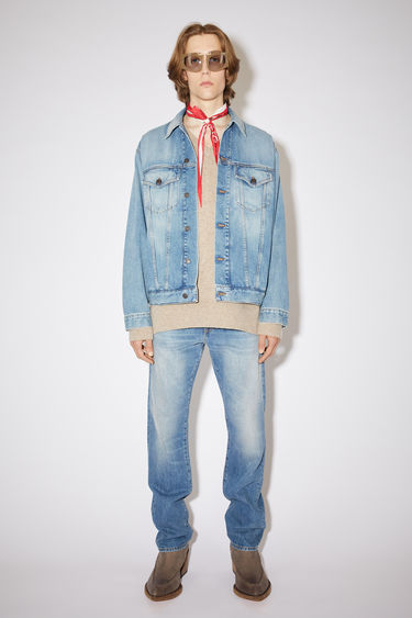 Acne Studios mid blue jacket is made of rigid cotton with a heavily worn vintage wash on organic Japanese broken twill denim.