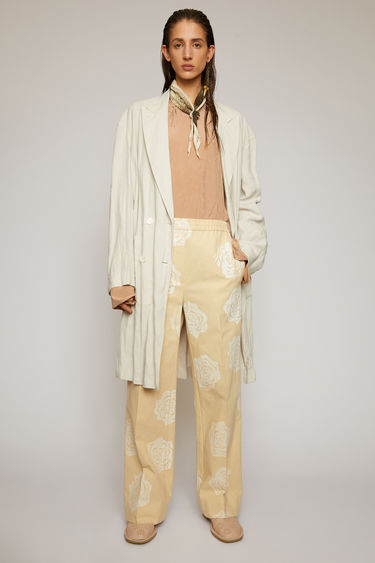 Acne Studios cream beige cotton-canvas trousers are cut to a straight-leg fit with an elasticated drawstring waistband and feature a graphic rose pattern on the front.
