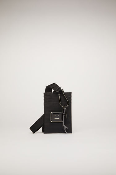Acne Studios black ripstop cardholder is adorned with a metal face-motif plaque and equipped with a detachable lanyard and a bottle opener.