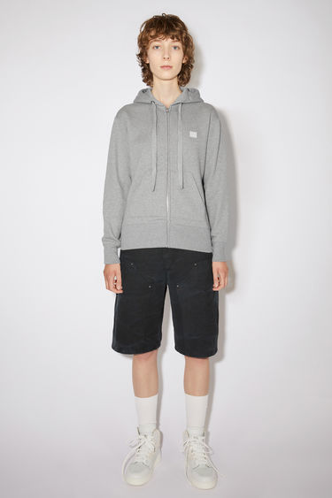 Acne Studios Ferris Zip Face light grey melange is a zip-through hooded sweatshirt made from midweight brushed jersey with kangaroo slip pockets and accented with a tonal face-embroidered patch on the chest.