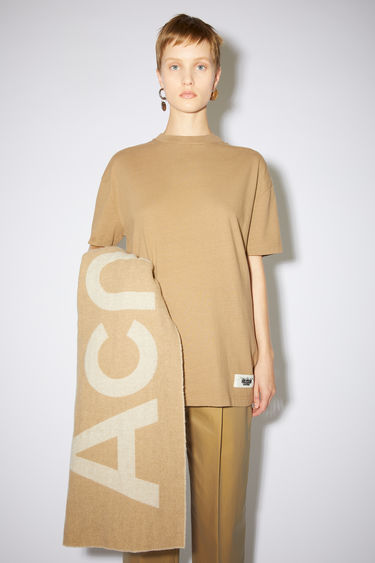 Acne Studios light brown crew neck t-shirt is made of organic cotton with an Acne Studios label on the lower front.