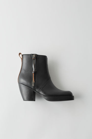 Acne Studios black boots with chunky stacked heel and zip puller.