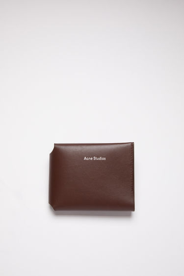 Acne Studios dark brown trifold card wallet is made of soft grained leather with a coin pocket, bill sleeve, and four card slots, featuring a silver stamped logo on the front.