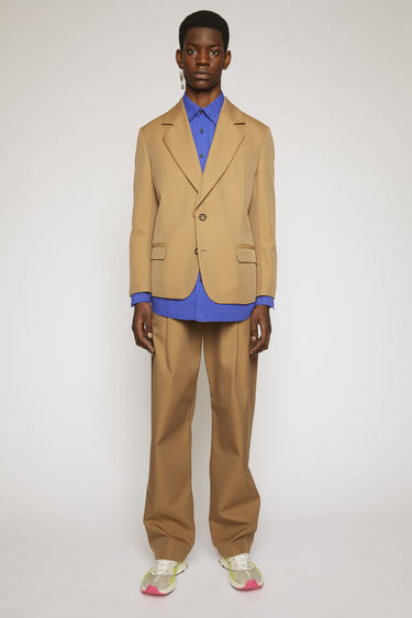 Acne Studios mushroom beige suit jacket is constructed with padded shoulders and wide lapels and features two ring button closures and neatly pressed creases on front darts.