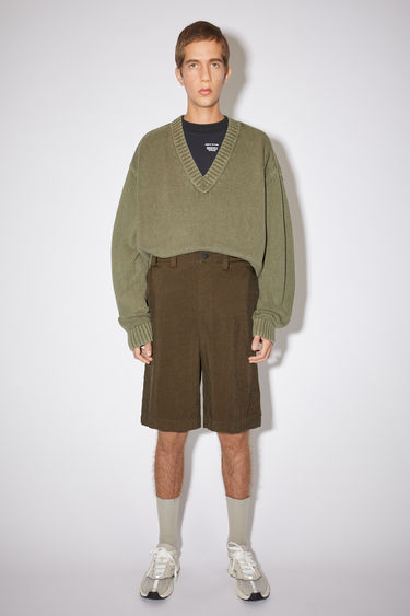 Acne Studios cedar green relaxed shorts are made of nylon with creased legs.