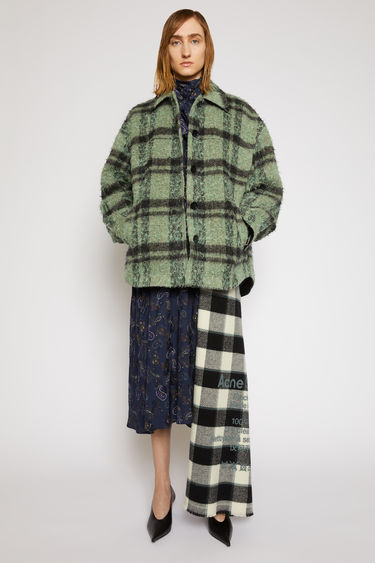 Acne Studios green/black checked overshirt is made from wool blended with alpaca and mohair for a textured handle, then crafted to an A-line shape with dropped shoulders and a curved hem.