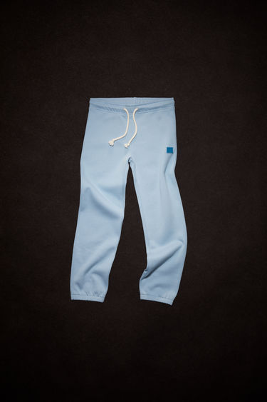 Acne Studios powder blue organic cotton sweatpants feature an elastic drawstring waist and tonal embroidered face patch on the front.