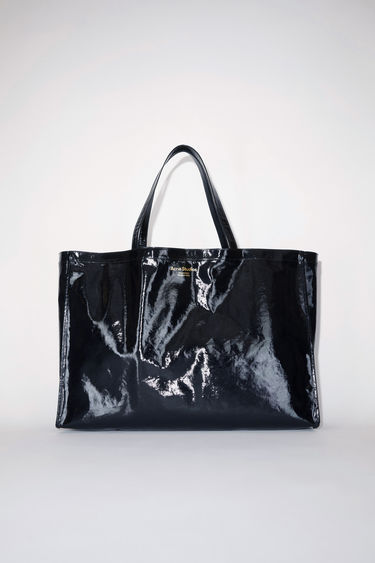 Acne Studios black oilcloth tote bag features Acne Studios branding.
