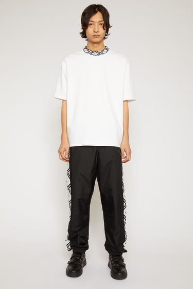 Acne Studios black track pants are crafted from nylon shell with an elasticated waist and hem and patterned with the house's face motif on the satin stripes.