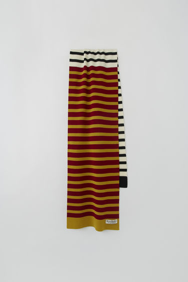 Acne Studios launches an exclusive range with Swedish artist Jacob Dahlgren. As part of the collaboration, the burgundy multi scarf is finely knitted from wool and patterned with horizontal stripes.