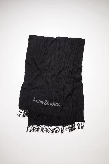 Acne Studios black scarf is crafted to a wide dimension from wool with crinkle effect and features a jacquard logo above the fringed edges.