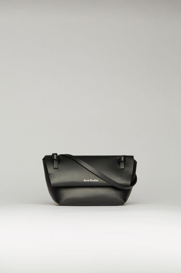 Acne Studios black mini purse crafted from soft-grained leather with a knotted shoulder strap. It has magnetic fastenings that open to reveal a tonal leather lining with a single slip pocket.
