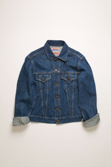 Acne Studios 1998 Dark Blue Trash jacket is crafted from rigid denim that's stonewashed to give a worn-in appeal. It's cut to a slim silhouette with chest patch pockets and accented with branded metal buttons.